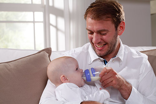 Feeding Bottle With NaturalWave™ Teat Used To Feed Baby By Dad